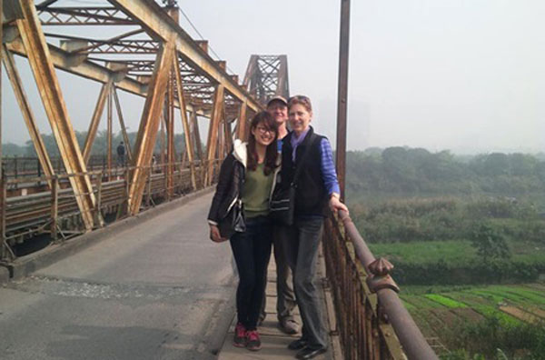 Bridging the gap: Phung Ngoc Phuong Linh (left) poses with tourists at Ha Noi's historic Long Bien Bridge. — Photo courtesy of HFTGs