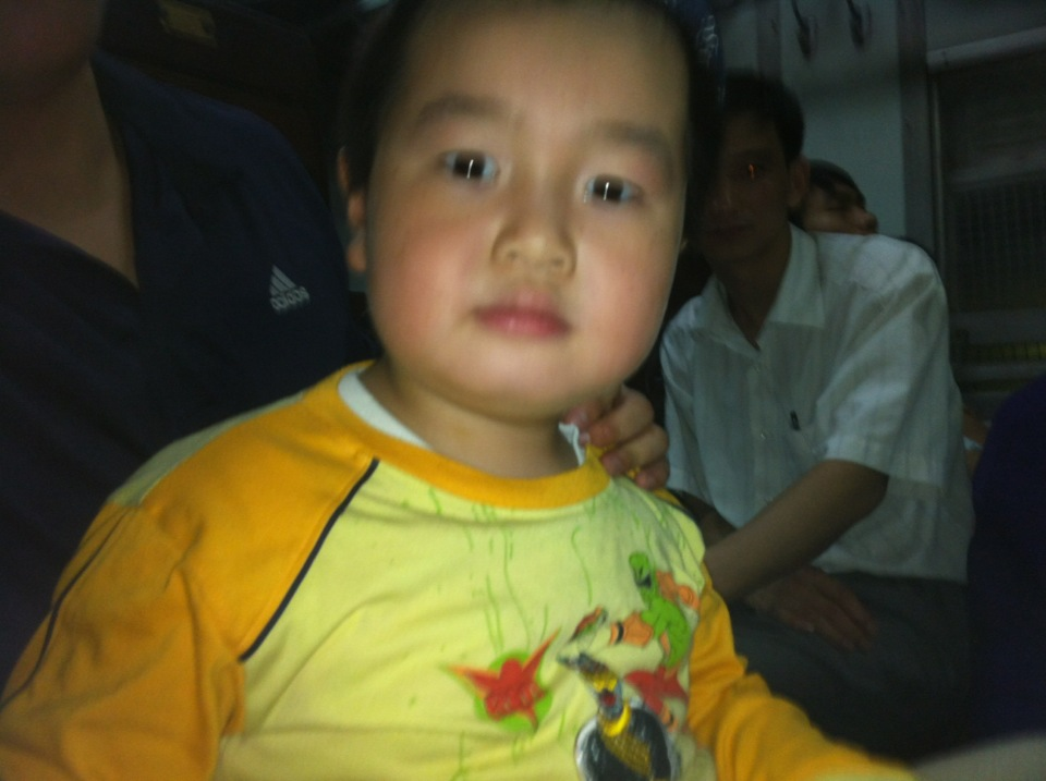 The little stranger sits with me on the train. The man behind with the white shirt is his uncle