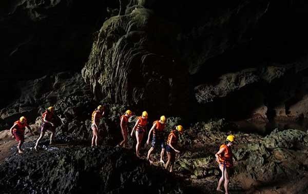 Туристы следовать только свет от факелов на лбу, чтобы двигаться внутри Toi пещере.