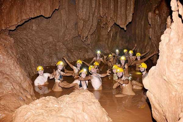 Группа туристов насладиться грязевые ванны внутри Toi пещере