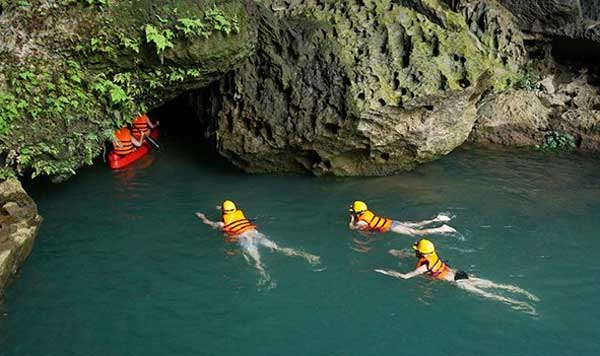 Tourists swim in the Chay River to Toi Cave after jumping down from the zip line